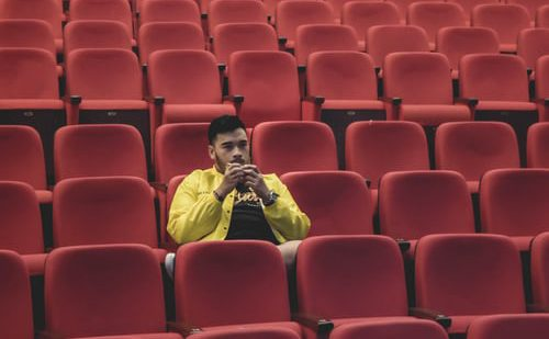 A person sits in an otherwise empty venue due to COVID-19