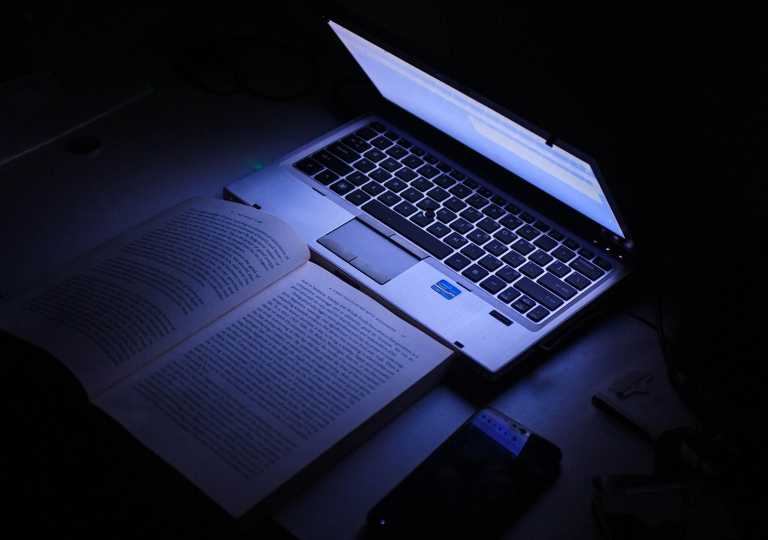 Open laptop next to an open book illustrating learning online with an LMS