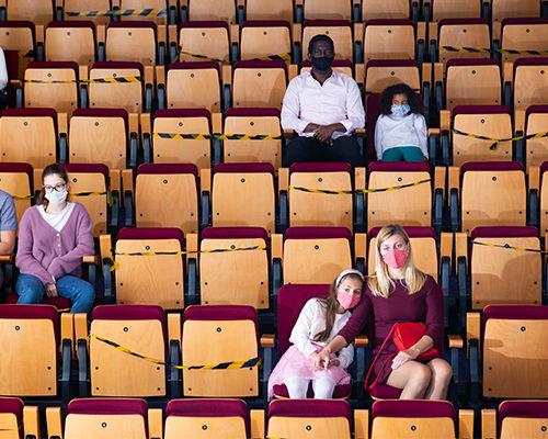 people in auditorium sitting far apart